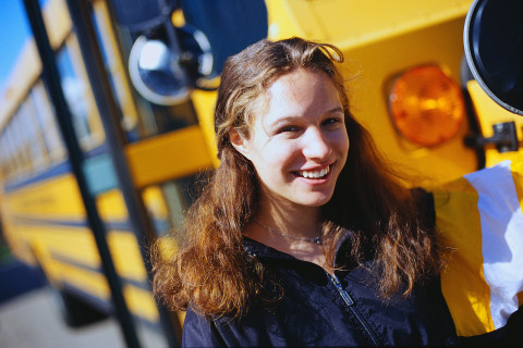 Student Standing by School Bus